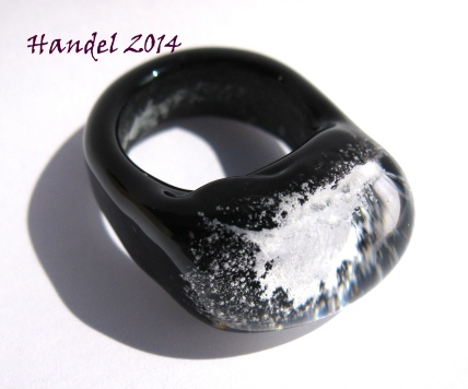 This ring made with black base and shank, with light blue glow dust, capped with lauscha glass